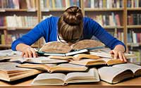 Young student with her head down on a pile of books.