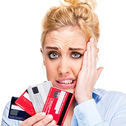 image of woman holding credit cards with a confused look