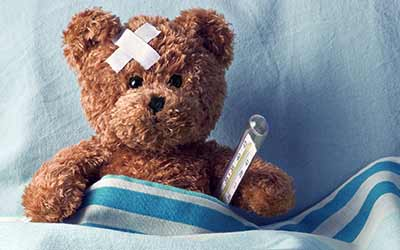 Image of a teddy bear in bed with a thermometer and bandages signifying financial stress affecting health.