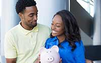 Young couple holding a piggy bank, discussing their finances.