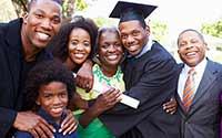 A family hugging, congratualting a college graduate.