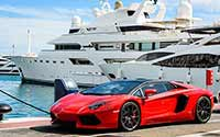 An expensive sports car in front of a yacht.