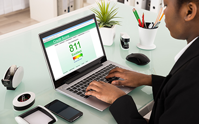 A woman looking at her credit score online, showing a great credit score of 811.