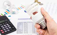Someone holding an energy-efficient lightbulb while calculating energy costs.