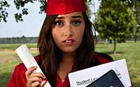 A young woman holding a diploma depressed about student loan debt.